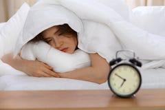 Schönes Schlafenim Bett morgens liegen der jungen Frau und sich entspannen Sonniger Tagesanfänge ist- die Zeit, eine Arbeit anzus stockfotos