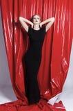 Schönes schlankes blondes Mädchen gekleidet in einem schwarzen passenden Kleid auf einem Hintergrund des roten Latexgewebes Moder stockfoto