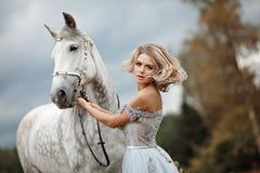 Schönes schlankes blondes Mädchen im Kleid, das einen Grauschimmel, heraus umarmt Stockbilder