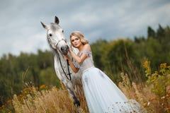 Schönes schlankes blondes Mädchen im Kleid, das einen Grauschimmel, outd umarmt Stockfotografie