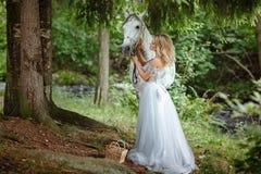 Schönes schlankes blondes Mädchen im Kleid, das einen Grauschimmel, outd umarmt Stockfotos