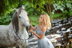 Schönes schlankes blondes Mädchen im Kleid, das einen Grauschimmel, outd umarmt Stockbild