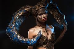 Schönes schlankes Mädchen in einem Anzug mit Hörnern für Halloween auf einem schwarzen Hintergrund Lizenzfreie Stockbilder