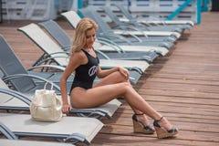 Schönes schlankes Mädchen in einem Badeanzug liegt auf einem deckchair Lizenzfreie Stockfotos