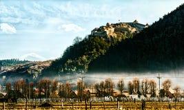 Schönes Schloss unter dem bewölkten Himmel auf einem Hügel über einer Stadt und einem Kirchhof Lizenzfreies Stockfoto