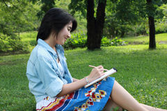 Schönes Schreiben der jungen Frau draußen in einem Park Stockfoto