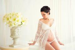 Schönes schwangeres im hellen weißen Spitzenegligé im Badezimmer Stockfoto