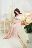 Schönes schwangeres Mädchen in einem Spitzenegligé, das auf einem Rosenbeet sitzt Lizenzfreie Stockfotografie