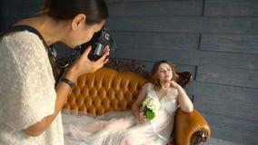 Schönes schwangeres vorbildliches Mädchen im weißen Kleid oder peignoir auf einem Trainer, der für Fotografen aufwirft stock video footage