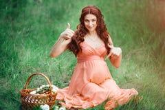 Schönes Schwangerschaftskonzept Glückliche Frau des Brunette, die auf Gras mit dem gelockten Haar auf Naturhintergrund sitzt Stockfotografie