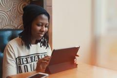 Schönes schwarzes Mädchen, das an Tablette im Café lächelt und arbeitet lizenzfreies stockfoto
