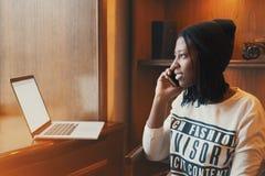 Schönes schwarzes Mädchen, das am Telefon im Café lächelt und spricht lizenzfreies stockfoto