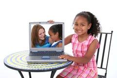 Schönes sechs Einjahreskind, das weg geliebtes im Laptop zeigt Stockfotografie