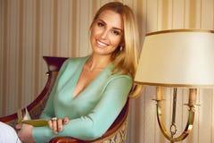 Schönes sexy blondes Geschäftsfrau-Lesebuch entspannen sich Stockfotografie
