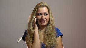 Schönes sexy blondes Mädchen in blaues Kleidersprechendem Telefon und erhalten angenehme Einladung im Studio stock video footage