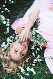 Schönes sexy blondes Mädchen, das auf dem Gras liegt Stockfoto