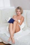 Schönes sexy blondes Mädchen, das ein Buch an liegt liest Stockfoto