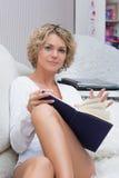 Schönes sexy blondes Mädchen, das ein Buch an liegt liest Lizenzfreies Stockfoto