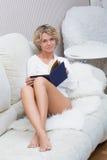 Schönes sexy blondes Mädchen, das ein Buch an liegt liest Lizenzfreie Stockfotos