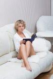 Schönes sexy blondes Mädchen, das ein Buch an liegt liest Stockfotos