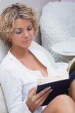 Schönes sexy blondes Mädchen, das ein Buch an liegt liest Stockfotografie