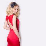Schönes sexy blondes Mädchen im roten langen Abendkleid mit Blumen in ihrer Haar- und Lockenfrisur Stockfotos