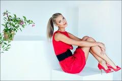 Schönes sexy blondes Mädchen mit blauen Augen in einem roten Kleidersitzen Stockfotografie