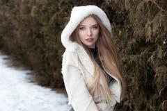 Schönes sexy blondes Mädchen mit dem langen Haar, volle Lippen in einem weißen Mantel gehend in das Winterholz Stockbilder