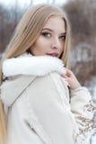 Schönes sexy blondes Mädchen mit dem langen Haar, volle Lippen in einem weißen Mantel gehend in das Winterholz Stockfotos