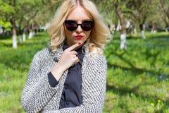 Schönes sexy blondes Mädchen mit den roten Lippen in der Sonnenbrille gehend in den Garten eines hellen sonnigen Tages Stockfotos