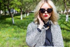 Schönes sexy blondes Mädchen mit den roten Lippen in der Sonnenbrille gehend in den Garten eines hellen sonnigen Tages Stockbild