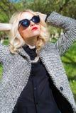 Schönes sexy blondes Mädchen mit den roten Lippen in der Sonnenbrille gehend in den Garten eines hellen sonnigen Tages Stockfotografie