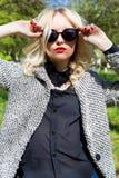 Schönes sexy blondes Mädchen mit den roten Lippen in der Sonnenbrille gehend in den Garten eines hellen sonnigen Tages Lizenzfreies Stockfoto
