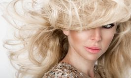 Schönes sexy blondes Modell mit erstaunlichen Augen, des Winds langes Volumenhaar unten im sexy eleganten Kleid Stockbild