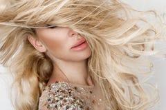 Schönes sexy blondes Modell mit erstaunlichen Augen, des Winds langes Volumenhaar unten im sexy eleganten Kleid Lizenzfreie Stockfotos