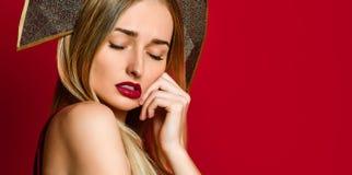 Schönes blondes russisches Mädchen in traditionellem kokoshnik Hut, festliches Kleid des Samts auf einem roten Hintergrund, stockfoto