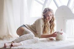 Schönes sexy blondes Sitzen im Fenster zusammen mit der Katze Stockfotos