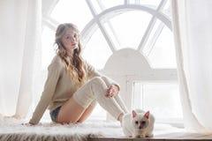 Schönes sexy blondes Sitzen im Fenster zusammen mit der Katze Stockfoto