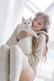 Schönes sexy blondes Sitzen im Fenster zusammen mit der Katze Lizenzfreie Stockfotos