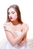 Schönes sexy Brunettemädchen mit den roten Lippen, die nackte Schultern einwickeln im weißen Stoff schaut unten auf einem Weiß si Stockfoto