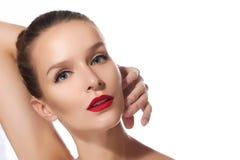 Schönes sexy Brunettemädchen mit perfektem rotem Lippenstift der blauen Augen der Haut auf einem weißen Hintergrund hob ihre Hand Lizenzfreie Stockbilder