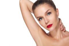 Schönes Brunettemädchen mit perfektem rotem Lippenstift der blauen Augen der Haut auf einem weißen Hintergrund hob ihre Hand Lizenzfreies Stockbild