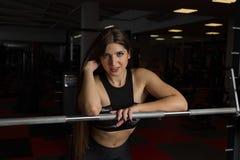 Schönes sexy Eignungsmodell, das emotional am athletischen Barbell in der Turnhalle aufwirft stockfotos