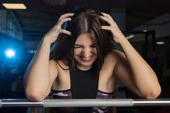 Schönes sexy Eignungsmodell, das emotional am athletischen Barbell in der Turnhalle aufwirft stockbilder