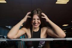Schönes sexy Eignungsmodell, das emotional am athletischen Barbell in der Turnhalle aufwirft stockfoto