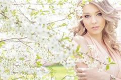 Schönes sexy elegantes süßes blauäugiges blondes Mädchen im Garten nahe den Kirschblüten an einem sonnigen hellen Tag Lizenzfreie Stockbilder