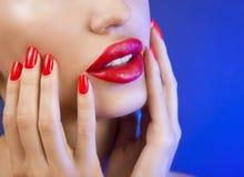 Schönes sexy junges Mädchen mit den roten Lippen und rotem Nagellack stockfotos