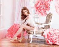 Schönes sexy Mädchen in einem langen Kleid mit, das den enormen rosa Blumen am Fenster sitzen ist Lizenzfreie Stockfotos