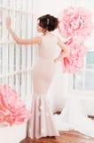 Schönes sexy Mädchen in einem langen Kleid mit enorme rosa Blumen Lizenzfreie Stockbilder
