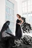 Schönes sexy Mädchen in einem langen Kleid mit enorme schwarze Blumen Lizenzfreies Stockfoto